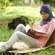 Beautiful young muslim lady leagain tree stump reading — Stock Photo #8817908