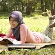Beautiful young muslim lady lie down reading — Stock Photo