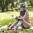 Beautiful young muslim lady sit on the mat reading — Stock Photo #8818389