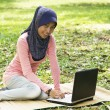 Beautiful young muslim lady sit on mat with notebook — Stock Photo #8818456