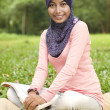 Beautiful young muslim lady smiling holding book — Stock Photo