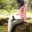 Beautiful young muslim lady sit on the stump reading — Stock Photo