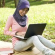Beautiful young muslim lady typing on laptop while sit on ma — Stock Photo #8818739