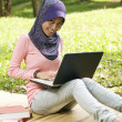 Stock Photo: Beautiful young muslim lady typing on laptop while sit on the ma