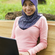 Beautiful young muslim smile infront of notebook - Stock Photo