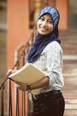 Beautiful young muslim lady smile while holding books at the bri — Stock Photo