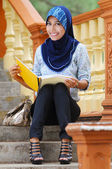 Bella signora giovane musulmano sorriso durante la lettura presso le scale — Foto Stock