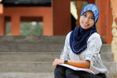 Beautiful young muslim lady smile while holding books at the par — Stock Photo