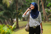 Beautiful young muslim lady smile while talk to the phone — Stock Photo