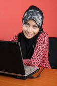 Beautiful young muslim smile infront of notebook — Stock Photo