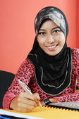 Beautiful young muslim smile while writing infront of notebook — Foto de Stock