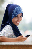 Beautiful young muslim smile while write text on mobile phone — Stock Photo