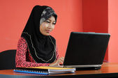 Beautiful young muslim woman busy with notebook on table — Stock Photo
