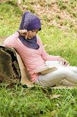 Vackra unga muslimska damen luta igen den stubbe som läser — Stockfoto