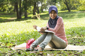Beautiful young muslim lady sit on the mat reading — Stock Photo