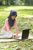 Beautiful young muslim lady sit on the mat with notebook — Stock Photo