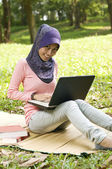 Beautiful young muslim lady typing on laptop while sit on the ma — Stock Photo