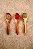Dried spices in wooden spoons. — Stock Photo