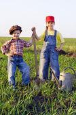Dwoje dzieci z łopatą i może — Zdjęcie stockowe