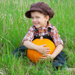 Smiling boy with pumpkin on the grass — Stock Photo