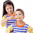 Girl teaches a boy to brush your teeth — Stock Photo