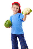 Smiling boy with cabbage and cauliflower — Stock Photo