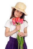 Smiling little girl with red tulips — Stock Photo