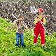 Two little children walking with tools — Stock Photo #8393476