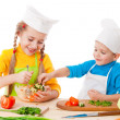 Two smiling kids mixing salad — Stock Photo