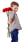 Smiling boy hiding a bouquet — Stock Photo