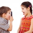 Boy looks at girl with a magnifying glass — Stock Photo