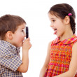 Boy looks at girl with a magnifying glass — Stock Photo #9323582