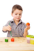 Smiling boy painting easter eggs — Stock Photo