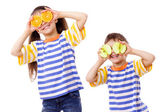 Two funny kids with fruits on face — Stock Photo