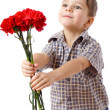 Smiling boy stretches forward a bouquet - Stock Photo