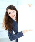 Happy smiling young business woman showing blank signboard, isolated on white background — Stock Photo