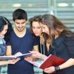 Skupina studentů mluví a držení poznámkové bloky — Stock fotografie