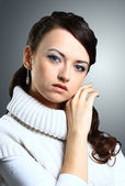 Thoughtful beautiful girl in sweater. Isolated on a gray background. — Stockfoto