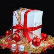 New year's eve decorated gift, with red balls on a black background - Stock Photo