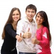 图库照片: Two girls and one guy show the thumbs up. Isolated on white background