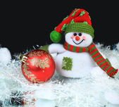 Toy snowman with festive red ball on a black background — Stock Photo