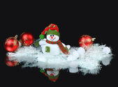 Toy snowman with a red festive ball and decorations, on a black background — Zdjęcie stockowe