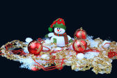 Toy snowman with a red festive balls and decorations, on a black background — Stock Photo