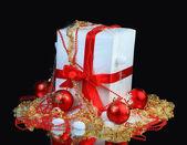 Cadeau de nouvel an décoré, avec des boules rouges sur fond noir — Photo