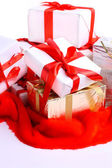 A lot of gifts with ribbons on the red cloth, on a white background. — Stock Photo