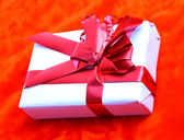 Gift box with a red ribbon on a red background. — Stock Photo