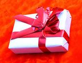 Caja de regalo con un lazo rojo sobre un fondo rojo. — Foto de Stock
