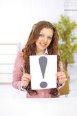 Business woman with an exclamation point in the office. — Stock Photo
