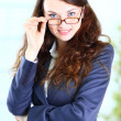 Portrait of a pretty young business lady in spectacles, smiling, in the off — Stock Photo