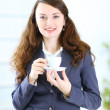 Business woman with a cup of coffee in the office — Stock Photo